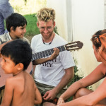 A Venezuelan kid plays Peter Maybarduk's nylon string guitar with a sun-blaeched Peter looking on.